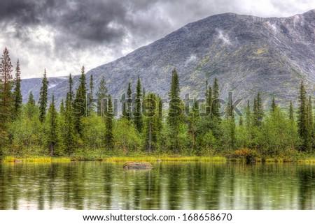 mountain landscape with lake, forest and clouds, rainy weather, HDR image(High Dynamic Range), Kola Peninsula, Khibiny mountains, Russia, 2014 - stock photo
