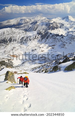 Mountain landscape with pair of climbers ascending on steep snowy slope  - stock photo