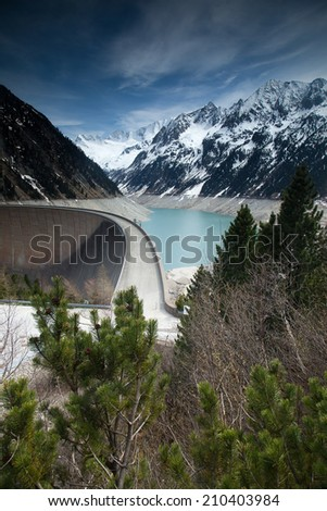 Mountain landscape with storage reservoir and snowy mountains