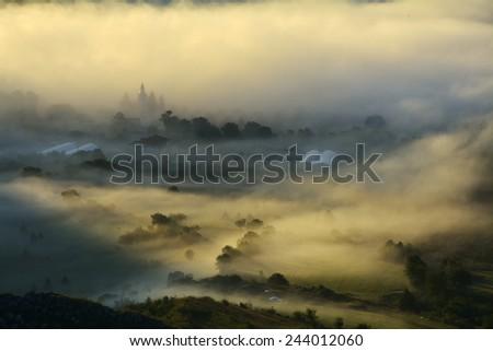 Mountain landscape with summer morning fog at sunrise - stock photo