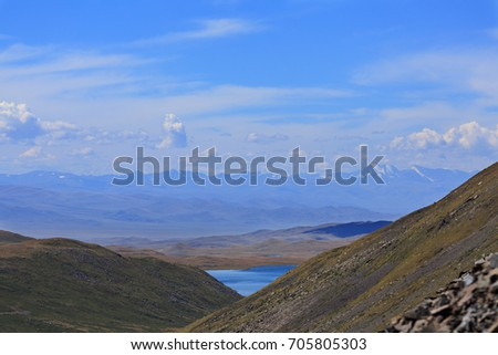 Mountain landscape with the blue lake in the valley and panoramic view on the snow-capped mountain range at the background. Exploring beautiful nature of Altai, Siberia, Russia