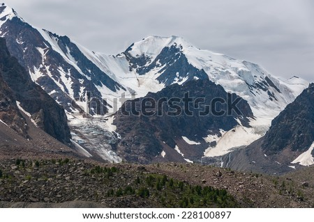 Mountain landscape with the image of the snow-capped mountains and glaciers on the background of cloudy sky