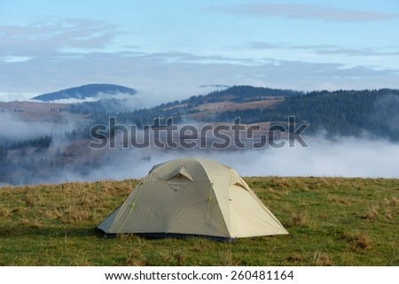 Mountain landscape with tourist tent on a meadow - stock photo