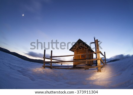 Mountain landscape with wooden villages. Winter evening. The path in the snow. Carpathians, Ukraine, Europe - stock photo