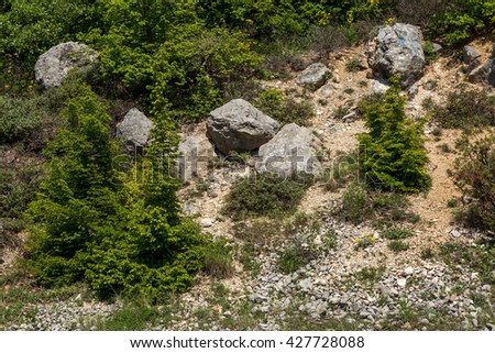Mountain landslide stone slopes threaten to block roads and forest roads. The danger for drivers and residents of the city at the foot of the dangerous rocky mountains - stock photo