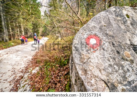 Mountain marker and hikers on a trail in the woods and mountain path. Children and parents hiking - active family lifestyle. - stock photo