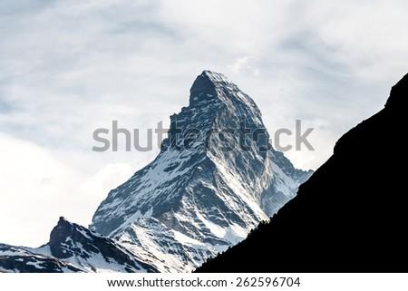 mountain Matterhorn, Alps, Zermatt, Switzerland with other silhouette mountain in front of Matterhorn - stock photo