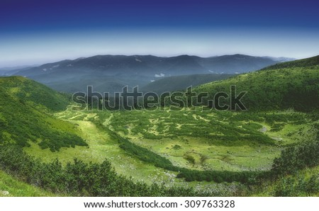 mountain meadow, view from above, below river, nature, summer, Carpathian mountains in the distance, Europe - stock photo