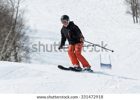 MOUNTAIN MOROZNAYA, YELIZOVO, KAMCHATKA, RUSSIA - APRIL 17, 2015: Young woman skier coming down the ski from mountain on a sunny day. Russian Federation, Far East, Kamchatka Peninsula. - stock photo
