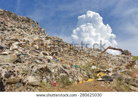 mountain of garbage with working backhoe - stock photo