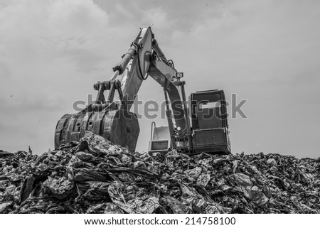 mountain of garbage with working backhoe, monochromatic - stock photo