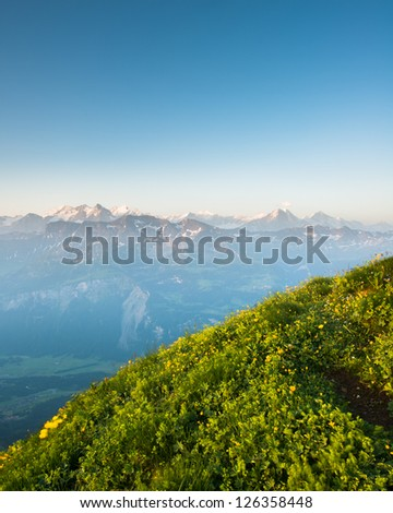 Mountain panorama from Brienzer Rothorn with green meadow and blue sky - stock photo