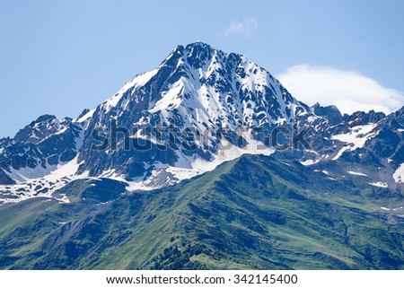 Mountain peak in snow and green hills below. Svaneti, Georgia - stock photo