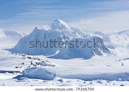 mountain peak is covered with white snow in Antarctica - stock photo