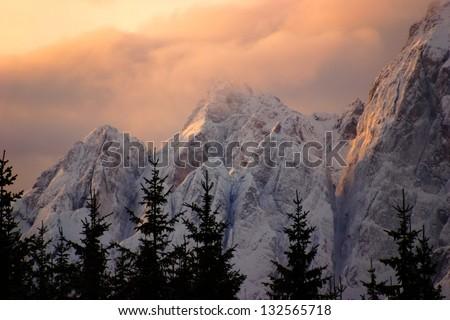 Mountain peaks at sunset in winter - stock photo