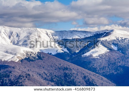 Mountain peaks covered with snow. Horizontal panoramic view with high mountains partial covered with snow and blue sky above covered with white clouds.