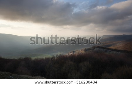 Mountain peaks in the clouds at dawn - stock photo