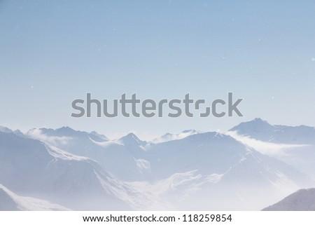 Mountain peaks of winter alps under blue sky - stock photo