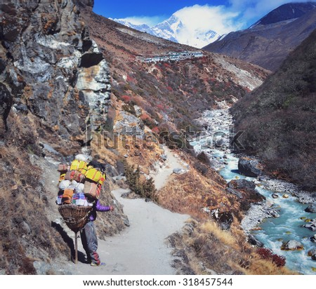 Mountain porter carrying heavy load in Himalayas,Everest region , Nepal - stock photo