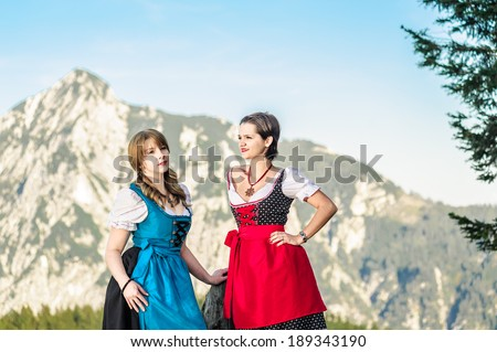 Mountain range and young woman with traditional austrian clothes