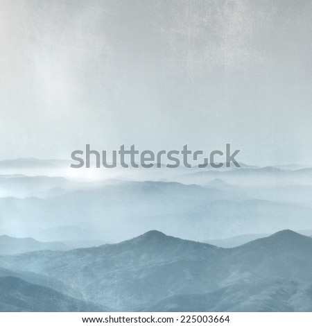 Mountain range in the fog - horizon background in grey blue vintage style - stock photo