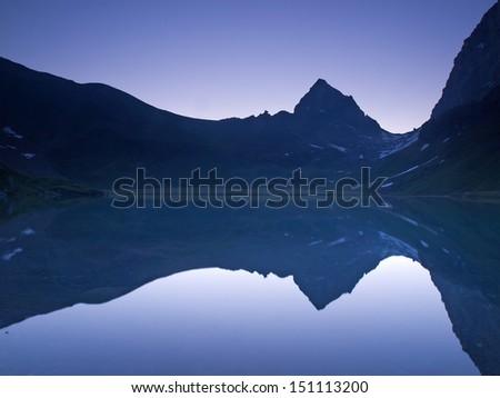 Mountain range mirroring at daybreak - stock photo