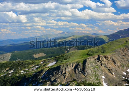 Mountain Range Vista  In Summer with Pine Trees and Snow on a Sunny Day with White Clouds - stock photo