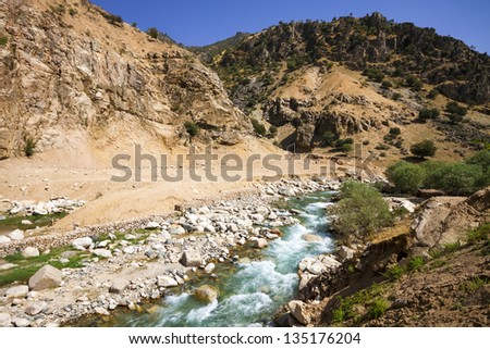 Mountain rapid river under blue sky in Central Asia - stock photo