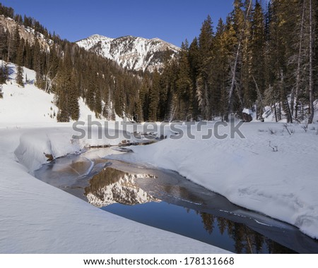 Mountain reflection in Granite canyon stream.  Mount Hunt is in the background.  Access from Jackson Hole Mountain resort. - stock photo