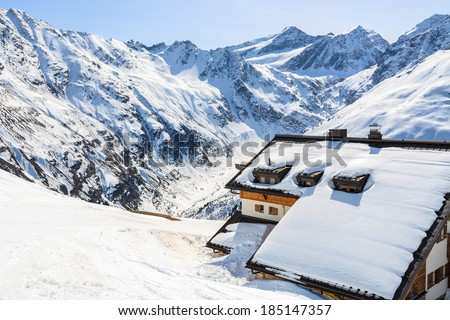 Mountain refuge hut covered with snow and peaks of Austrian Alps in background, Riffelsee ski resort in Pitztal valley