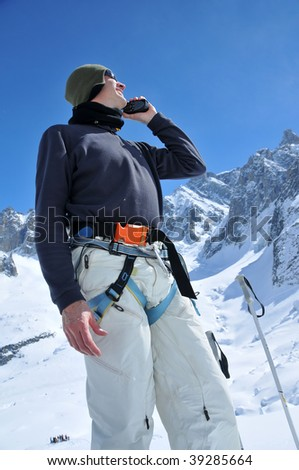 mountain rescue personnel on a glacier use a walkie talkie to locate a victim of a climbing accident. Around his waist a radio beacon, detector and locator.