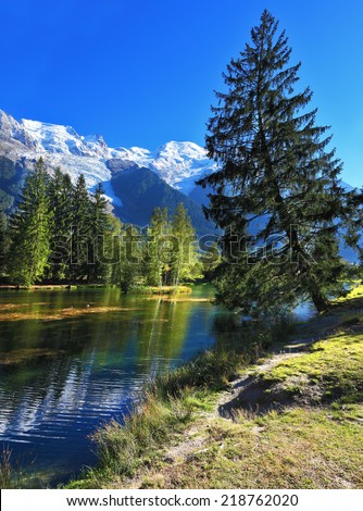 Mountain resort of Chamonix. Dreamlike beauty lake and park. In smooth water reflected snow-capped mountains - stock photo
