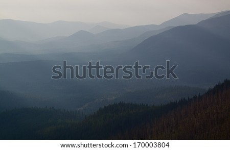 Mountain Ridges and Peaks, backlit with visible sun rays illuminating the scene wooded habitat of the Pacific Northwest, showing signs of a recent forest fire - burned trees in foreground - stock photo