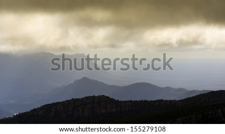 Mountain ridges in light and shadow under a stormy sky