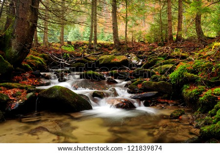 Mountain river in late Autumn, trees in background - stock photo