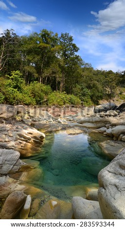 Mountain river in the Himalayas flows among the rocky stones steep shores - stock photo
