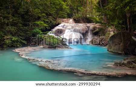 Mountain river stream flows through tropical forest and falls from cascades and waterfalls in wild lake with blue water - stock photo