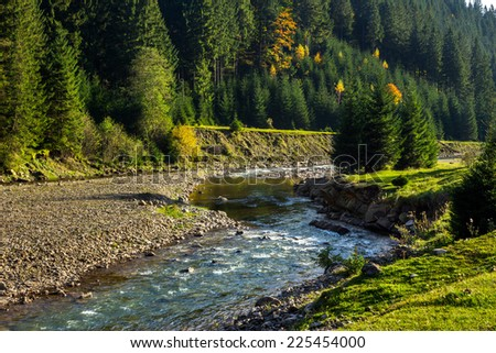mountain river with stones in the forest near the mountain slope - stock photo