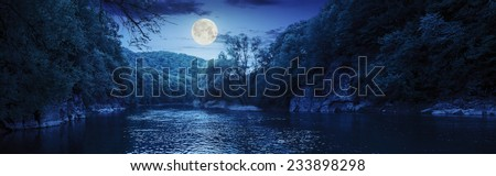 mountain river with stones on the shore in the forest near the mountain slope at night in full moon light - stock photo