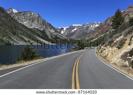 Mountain road along Lundy Lake in eastern Sierra Nevada mountains, California - stock photo