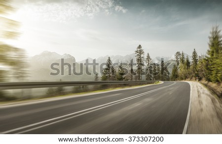 Mountain road at hight speed drive downhill - stock photo