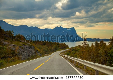 Mountain road at sunset with dramatic sky
