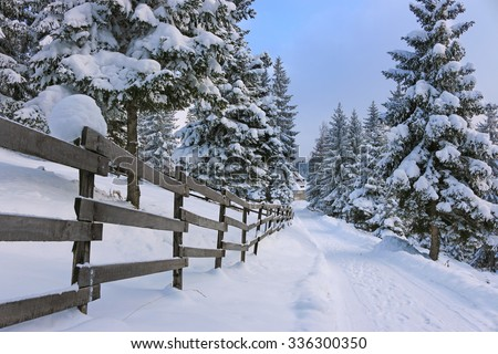 Mountain road covered by snow at countryside. Winter landscape with snowed trees, and wooden fence - stock photo