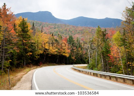 Mountain Road in autumn forest - stock photo