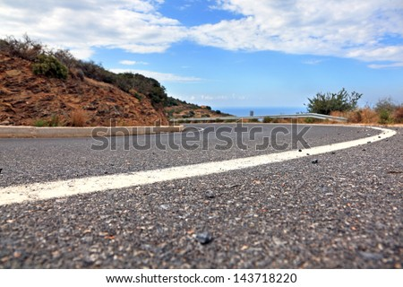 Mountain road in Crete, Greece. Low angle view. Shallow DOF. - stock photo