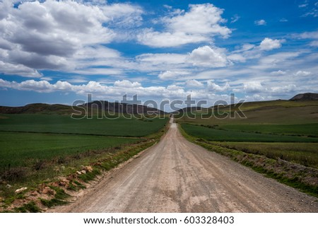 Mountain road leading to big mountains with a cloudy blue sky