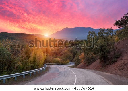 Mountain road passing through the forest with dramatic colorful sky and red clouds at colorful sunset in summer. Mountain landscape with road. travel background - stock photo