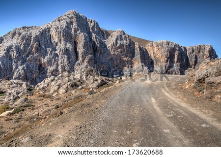 Mountain road winding past rugged rocky cliffs forming a mountain summit against a hot sunny blue sky - stock photo