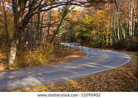 Mountain road winds through sunlit autumn forest. - stock photo