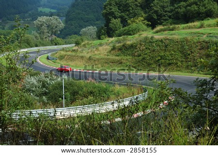 mountain road with a car in the forest - stock photo